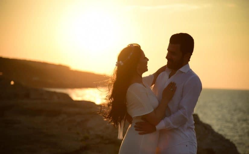 Phasen einer Beziehung - das Verliebtsein, die Liebe und Partnerschaften. Ein Paar, ganz in weiß gekleidet, steht an einem schroffen Meeresstrand schaut sich verliebt an